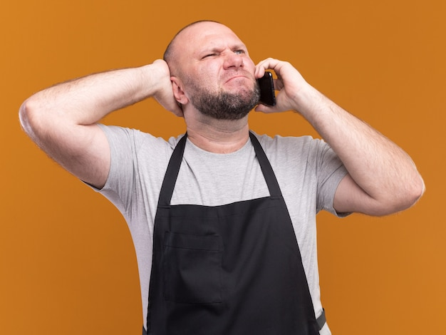 Il barbiere maschio di mezza età slavo in uniforme parla al telefono e mette la mano dietro la testa isolata sul muro arancione