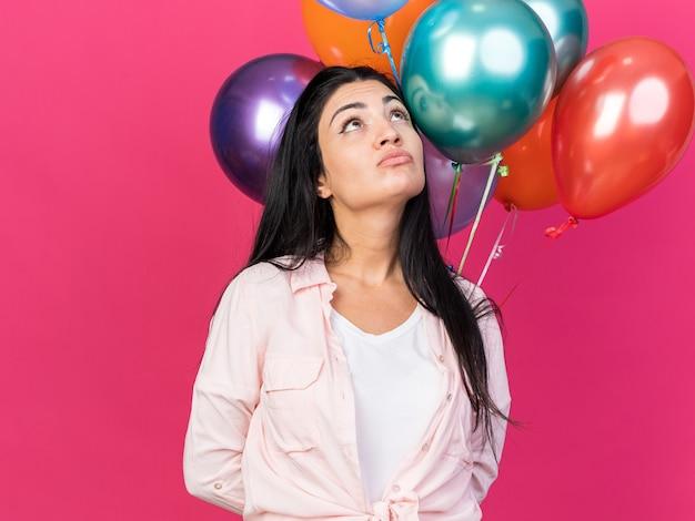 ピンクの壁に分離された風船を保持している若い美しい少女を探して不機嫌