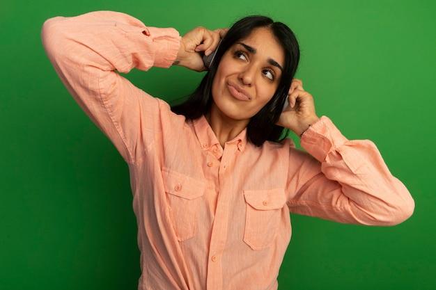 Недовольный глядя вверх молодая красивая девушка в розовой футболке с наушниками изолирована на зеленой стене