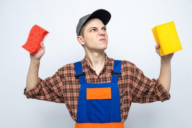 Недовольно глядя вверх молодой уборщик в униформе и кепке с губками