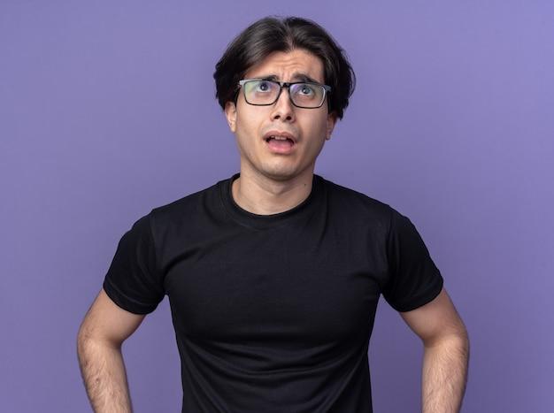 검은 티셔츠와 보라색 벽에 고립 된 안경을 쓰고 젊은 잘 생긴 남자를 찾고 불쾌한