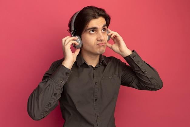 ピンクの壁に分離されたヘッドフォンで黒のtシャツを着ている若いハンサムな男を探して不機嫌