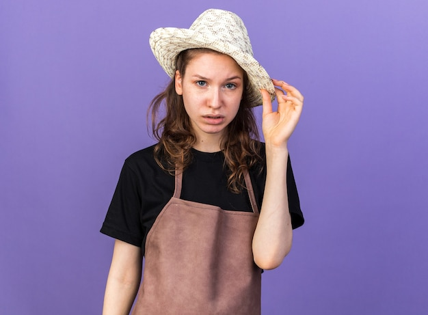 Недовольно выглядящая молодая женщина-садовник в садовой шляпе, держащая шляпу, изолированную на синей стене