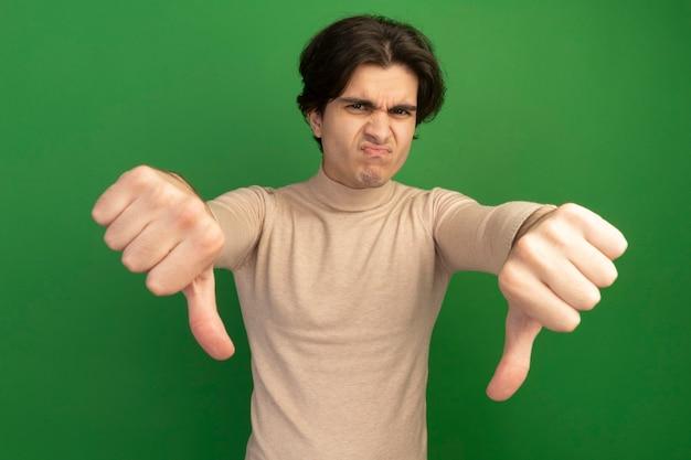 Ragazzo bello giovane sembrante dispiaciuto che mostra i pollici giù isolati sulla parete verde