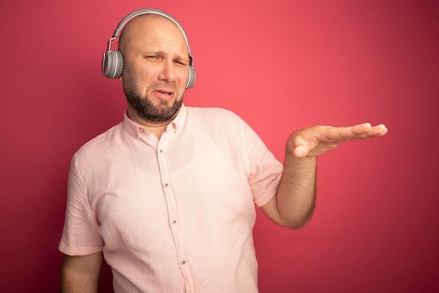 Недовольный лысый мужчина средних лет в розовой футболке и наушниках, показывающий размер