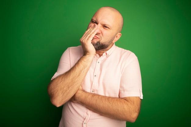 Sgradevole uomo calvo di mezza età che indossa la bocca coperta di maglietta rosa con la mano