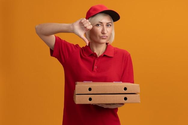 Una donna delle consegne bionda di mezza età scontenta in uniforme rossa e berretto che tiene in mano i pacchetti di pizza che mostra il pollice verso il basso