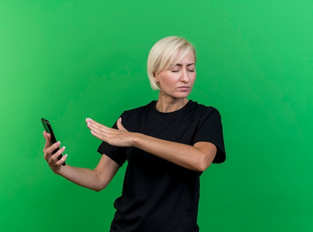 Unpleased middle-aged blonde slavic woman holding mobile phone keeping hand in air doing no gesture with closed eyes isolated on green background with copy space