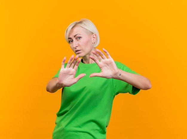 黄色の背景に分離されたジェスチャーをしないカメラを見て不機嫌な中年金髪スラブ女性