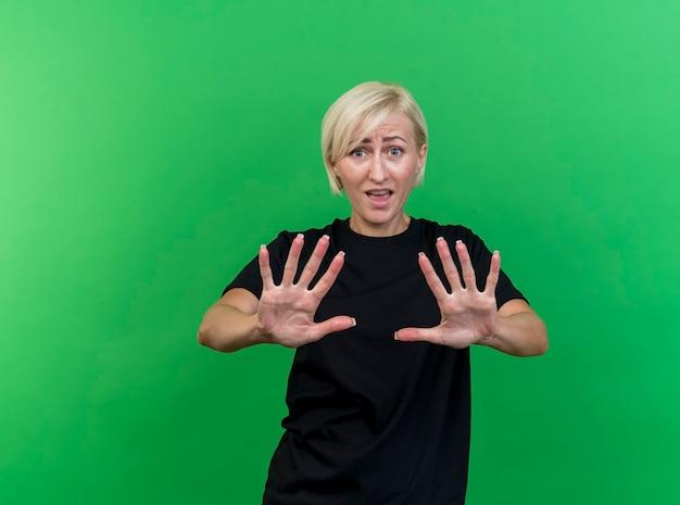 Donna slava bionda di mezza età dispiaciuta che guarda l'obbiettivo che non fa alcun gesto isolato su priorità bassa verde con lo spazio della copia