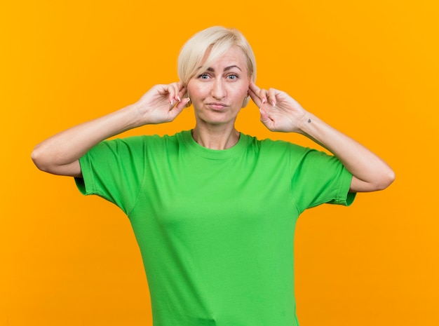 Unpleased middle-aged blonde slavic woman looking at camera keeping fingers on ears isolated on yellow background