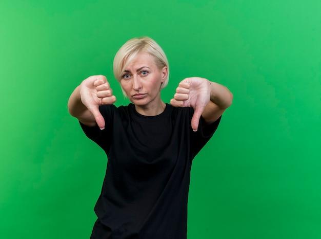 Donna slava bionda di mezza età dispiaciuta che mostra i pollici giù isolato sulla parete verde con lo spazio della copia