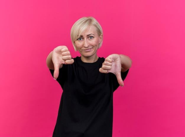 복사 공간이 진홍색 벽에 고립 엄지 손가락을 보여주는 불쾌한 중년 금발 슬라브 여자