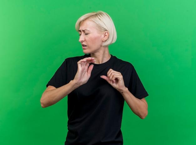 복사 공간이 녹색 배경에 고립 된 닫힌 눈으로 제스처를하지 않고 머리를 돌리는 불쾌한 중년 금발 슬라브 여자