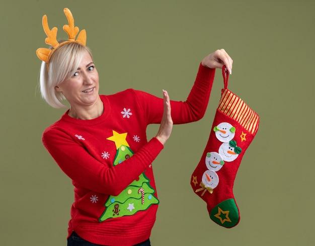 크리스마스 순록 뿔 머리띠와 크리스마스 스타킹을 들고 크리스마스 스웨터를 입고 불쾌한 중년 금발의 여자가 올리브 녹색 벽에 고립 된 거부 제스처를 하 고 찾고