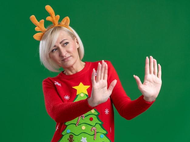 Недовольная блондинка средних лет в рождественской повязке на голову из оленьих рогов и рождественском свитере смотрит в сторону, делая отказный жест, изолированный на зеленом фоне