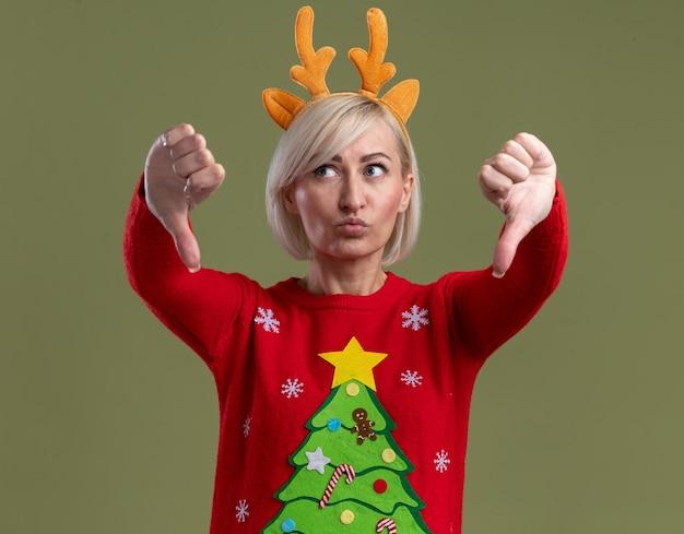 Недовольная блондинка средних лет в рождественской повязке на голову из оленьих рогов и рождественском свитере смотрит в сторону, показывая большие пальцы вниз со сжатыми губами, изолированными на оливково-зеленом фоне