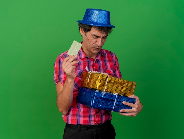 Unpleased middle-aged caucasian party man wearing party hat holding gift packs and credit card looking at gift packs isolated on green background with copy space