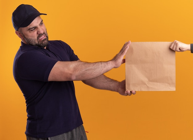 Unpleased middle-aged delivery man in uniform and cap giving paper food package to client isolated on yellow wall