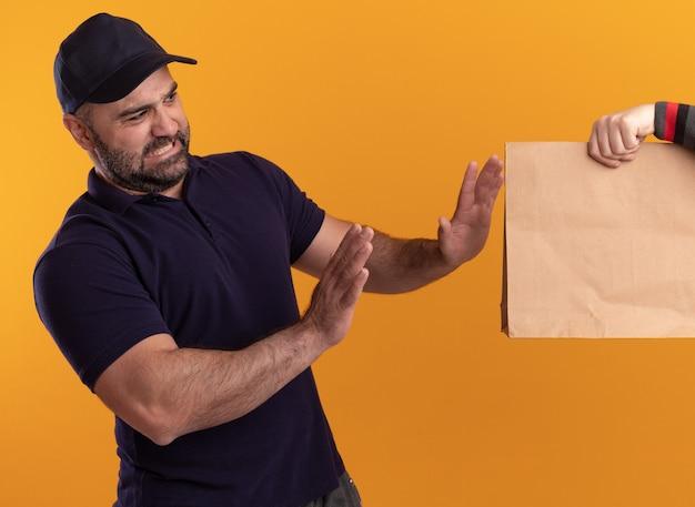 Uomo di consegna di mezza età dispiaciuto in uniforme e cappuccio che dà il pacchetto di cibo di carta al cliente isolato sulla parete gialla