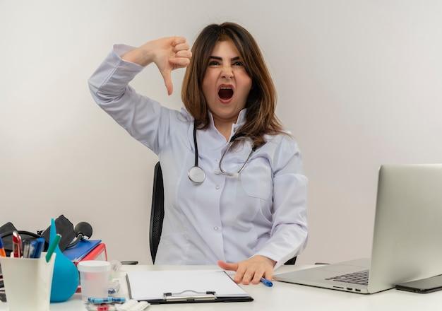 Недовольная женщина-врач средних лет в медицинском халате и стетоскопе сидит за столом с медицинскими инструментами, буфером обмена и ноутбуком, показывая изолированный палец вниз