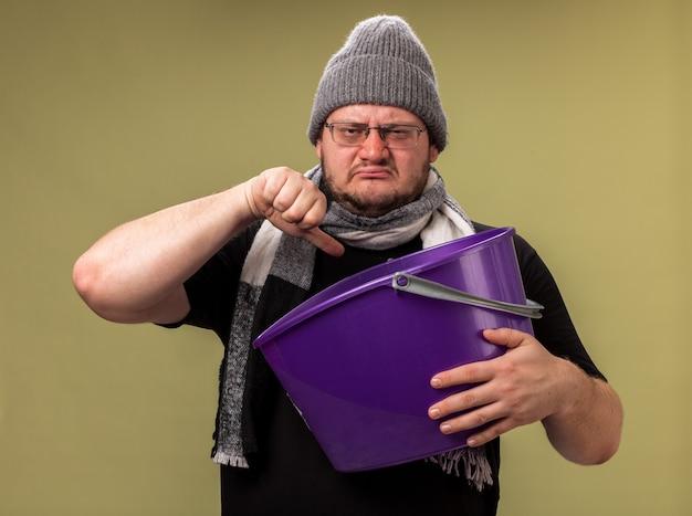 冬の帽子とスカーフを身に着けている不機嫌な中年の病気の男性は、オリーブグリーンの壁に隔離された親指を下に示すプラスチック製のバケツを保持しています