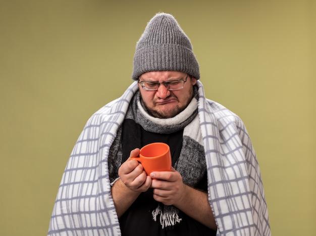 Maschio malato di mezza età scontento che indossa cappello invernale e sciarpa avvolta in un plaid che tiene e guarda una tazza di tè