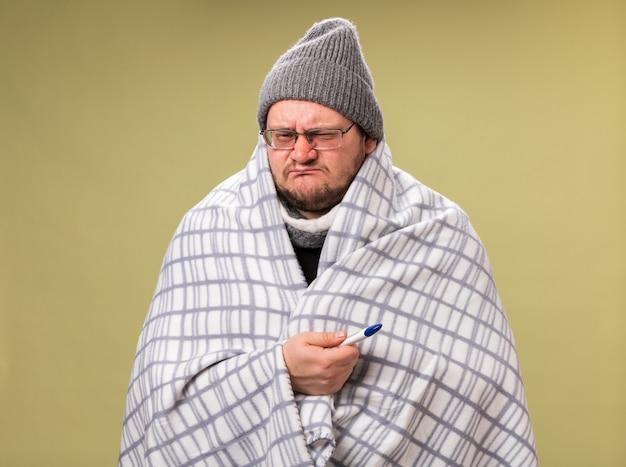 Un maschio malato di mezza età scontento che indossa un cappello invernale e una sciarpa avvolta in un termometro che tiene in mano un plaid