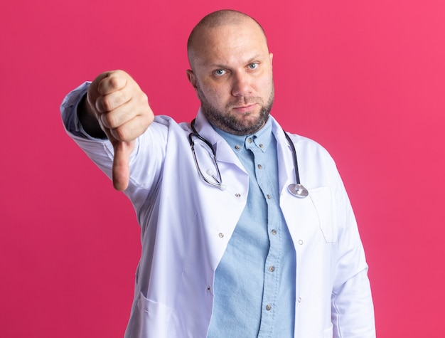 Unpleased middle-aged male doctor wearing medical robe and stethoscope looking at front showing thumb down isolated on pink wall
