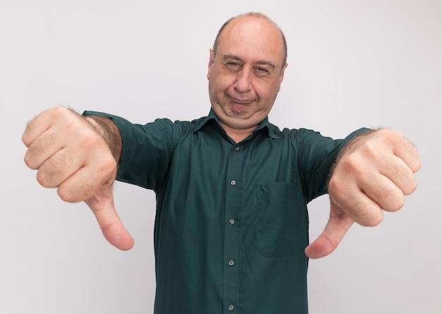 白い壁に隔離された親指を下に見せて緑のtシャツを着ている不機嫌な中年男性