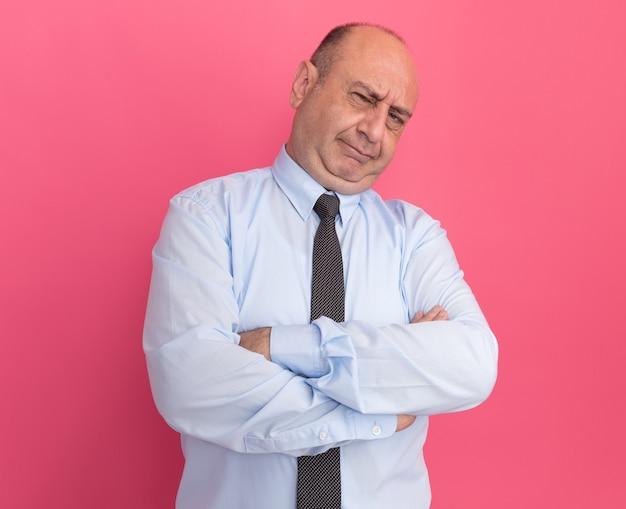 Uomo di mezza età scontento che indossa una t-shirt bianca con cravatta che incrocia le mani isolate sul muro rosa