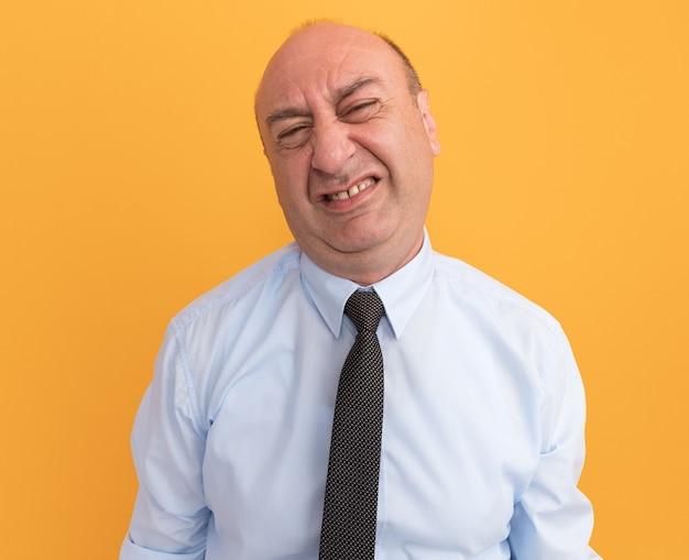 Недовольный мужчина средних лет в белой футболке с галстуком на оранжевой стене