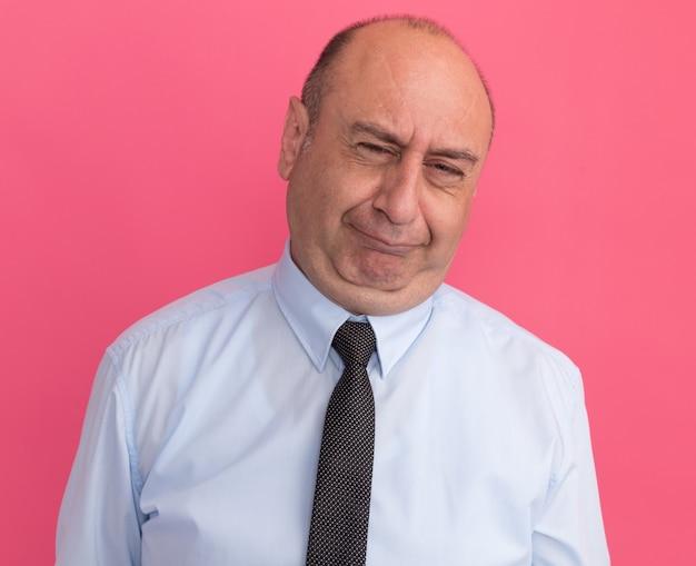 Недовольный мужчина средних лет в белой футболке с галстуком на розовой стене