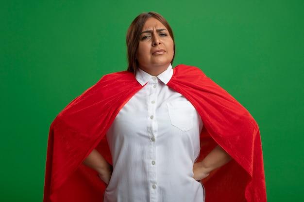 緑の背景に分離された腰に手を置く不愉快な中年のスーパーヒーローの女性