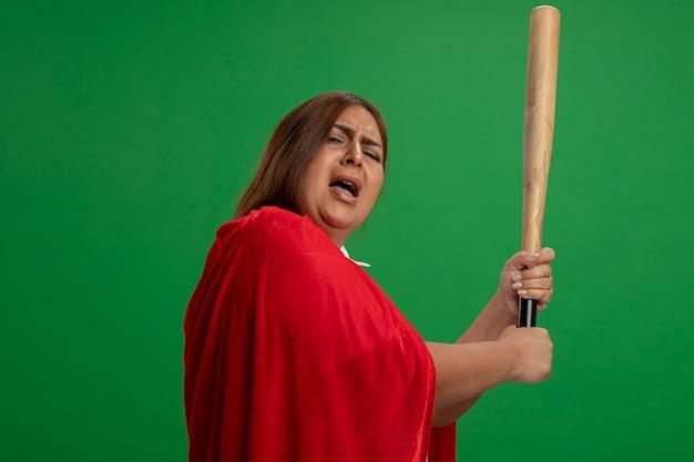Недовольная женщина супергероя средних лет поднимает бейсбольную биту на зеленом фоне