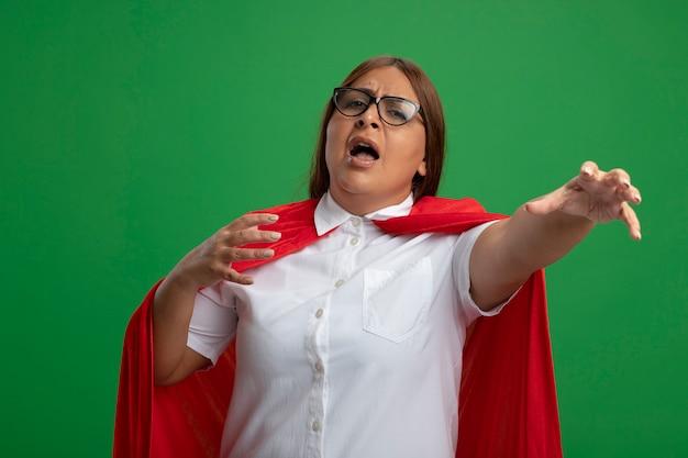 Donna di mezza età sgradevole del supereroe con gli occhiali che tiene la mano alla macchina fotografica isolata su fondo verde