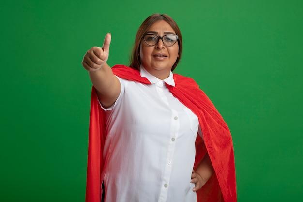 Sgradevole supereroe di mezza età femmina con gli occhiali che mostra il pollice in alto isolato su sfondo verde