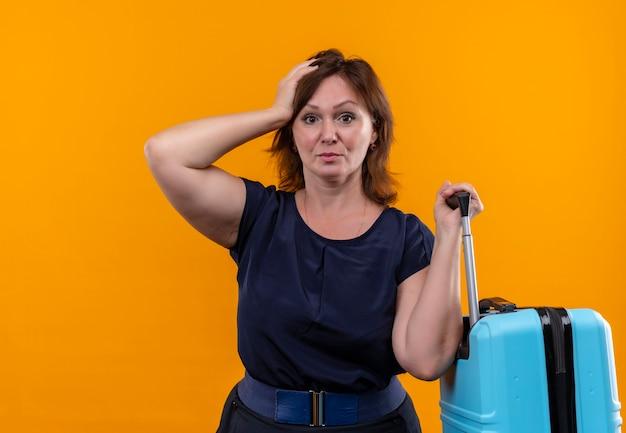 Donna di mezza età sgradevole del viaggiatore che tiene la valigia e che mette la mano sulla testa sull'arancio isolato