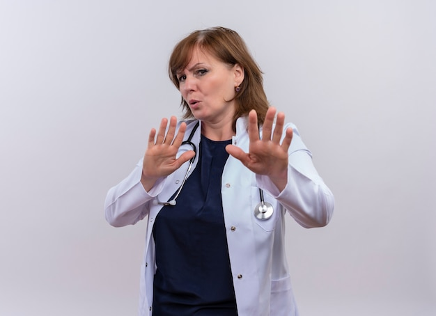 不快な中年女性医師医療ローブとコピースペースと分離の白い背景の上の停止のジェスチャーを行う聴診器を着ています。