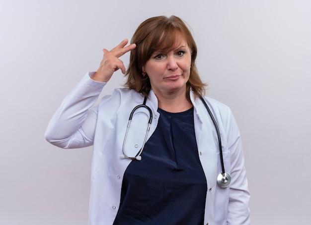 医療ローブと孤立した白い背景の上の頭の近くに手を置く聴診器を着て不快な中年女性医師
