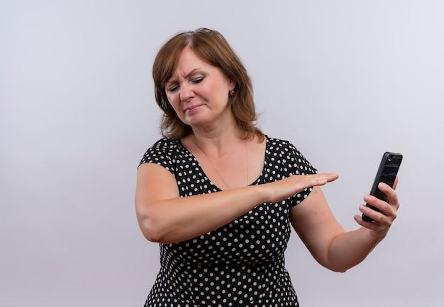 携帯電話を押しながら孤立した白い背景にそれを手で指している不快な中年女性