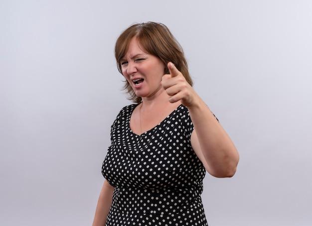孤立した白い背景の上のカメラで指で指している不快な中年女性