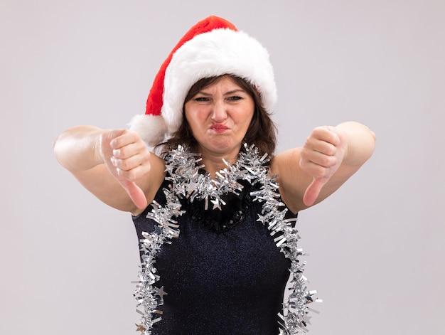 Недовольная женщина средних лет в новогодней шапке и мишурной гирлянде на шее, глядя в камеру, показывает палец вниз на белом фоне