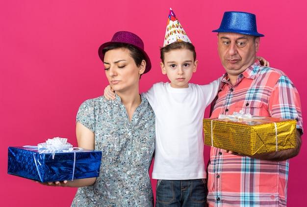 Madre e padre scontenti con cappelli da festa che tengono e guardano scatole regalo in piedi con il figlio isolato sul muro rosa con spazio copia copy
