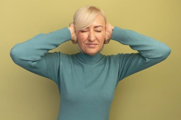 La donna slava abbastanza bionda sgradita chiude le orecchie con le mani sul verde oliva