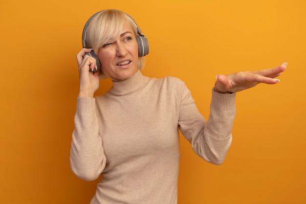헤드폰에 불쾌한 예쁜 금발의 슬라브 여자가 보이고 오렌지에 손으로 측면을 가리 킵니다.