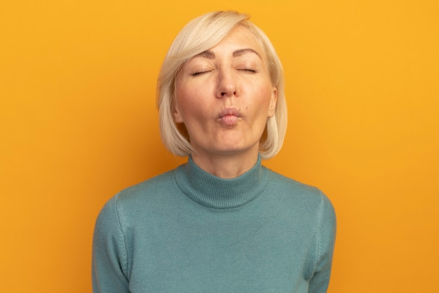 Недовольная симпатичная славянская блондинка, стоящая с закрытыми глазами на оранжевой стене