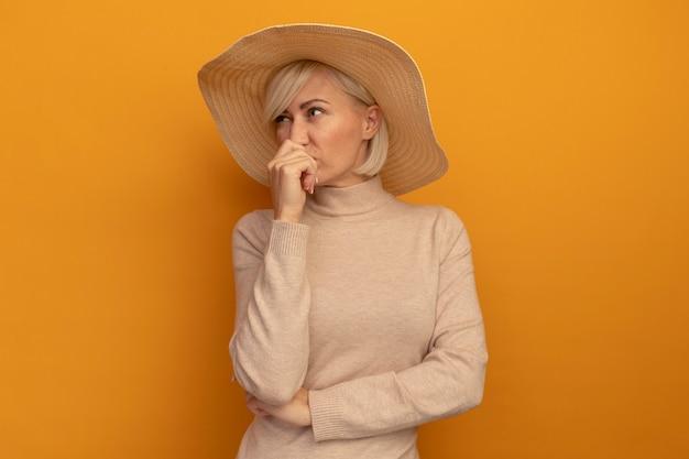ビーチ帽子をかぶった不機嫌そうなかなり金髪のスラブ女性は、オレンジ色の壁に隔離された口の前で手を握ります
