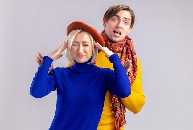 彼の首にスカーフを持ったハンサムなスラブ人の前に立っている彼女の頭に手を置くベレー帽を持つ不機嫌なきれいなブロンドの女性