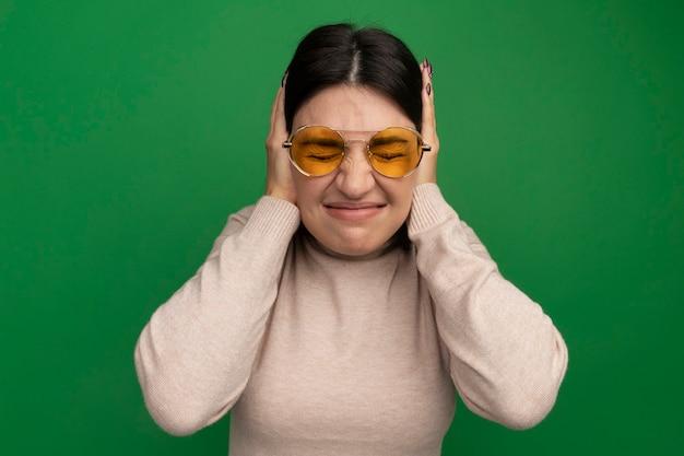サングラスをかけた不機嫌なかなりブルネットの白人の女の子は、緑の手で耳を閉じます